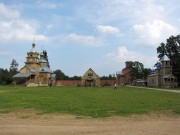 Общий вид построек Никандровой пустыни (Порховский район Псковской области) с западной стороны. Слева церковь Царственных новомучеников, на дальнем плане в центре Благовещенский собор, справа церковь Взыскания Погибших.