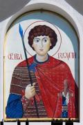Успенская церковь-часовня на Центральном кладбище города Сочи. Образ Георгия Победоносца над входом.